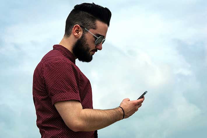 Man standing outdoor and texting on his phone