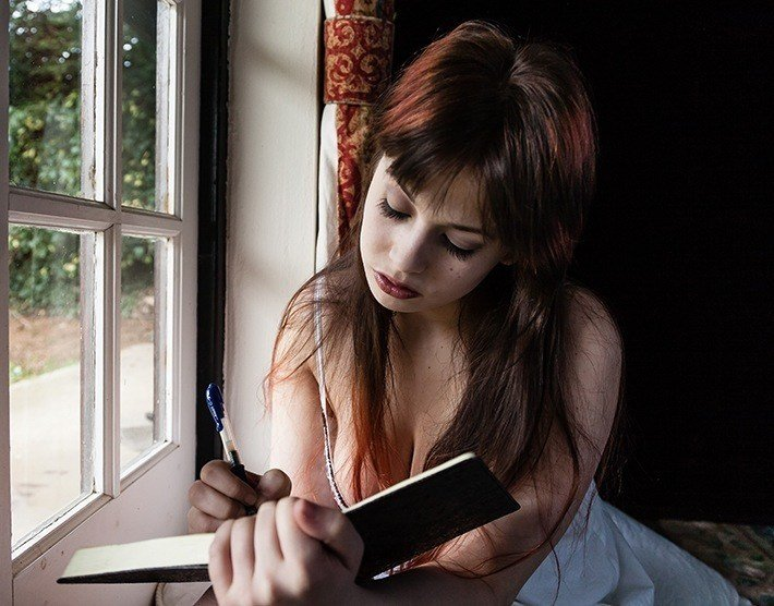 Sad woman sitting at the window and writing a letter