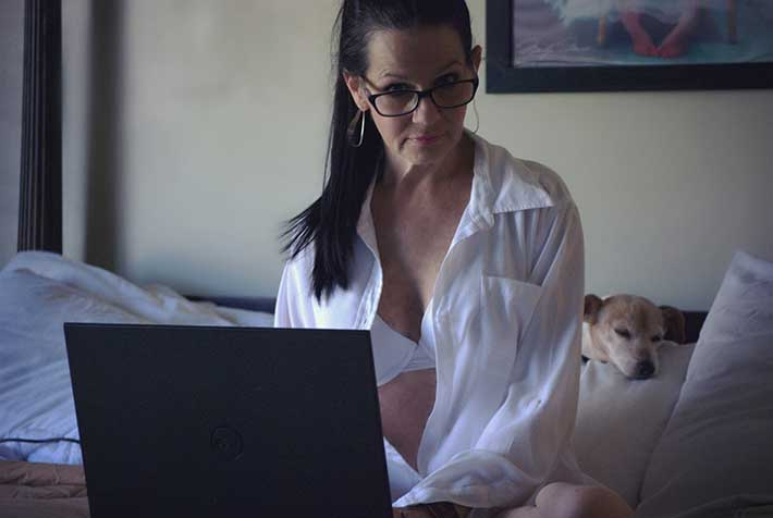 Middle aged woman with laptop in bed wearing white bra and white shirt