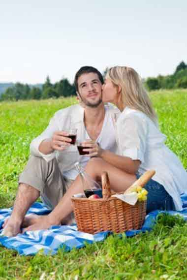 Woman kissing a happy man while having a picnic