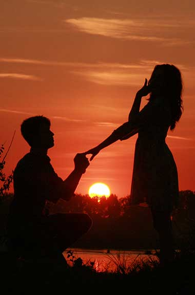 Silhouette of a man proposing marriage to a woman at sunset on the beach