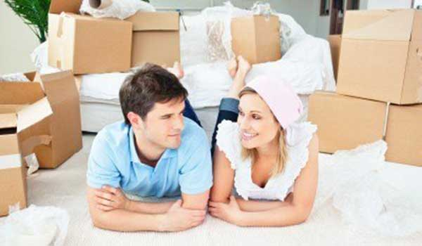 happy couple lying on the floor of their new home surrounded with boxes