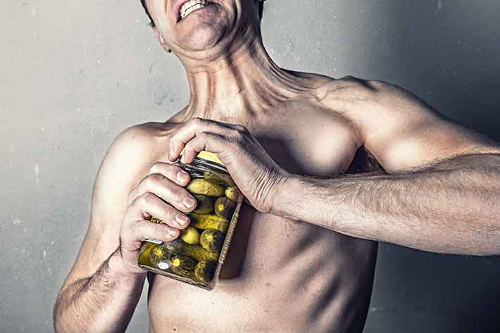 Funny photo of a man trying to open a jar of pickles