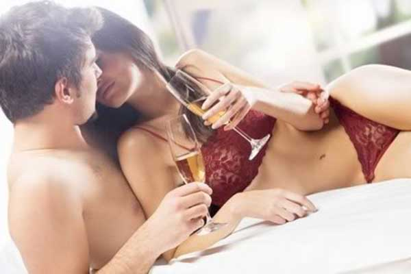 Intimate couple in bed with a glass of champagne in their hands