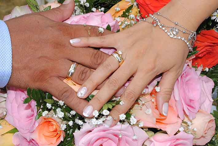 Woman and man touching hands, both wearing wedding rings