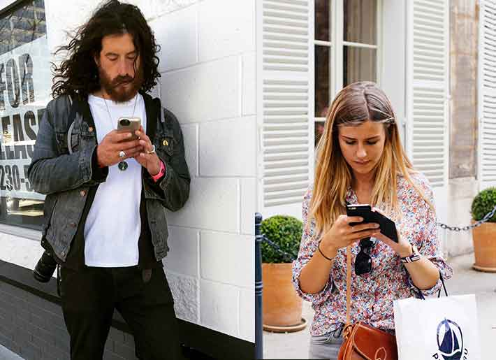 Sad man and woman standing in different places and reading text messages on their mobile phones