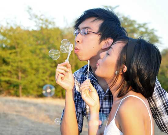Young couple having fun making soap bubbles