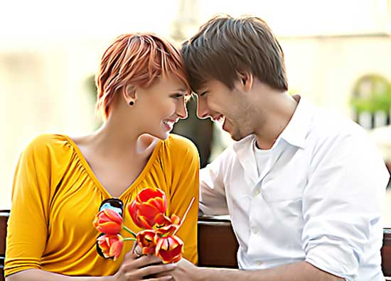 Young couple in love sitting on a bench and smiling to each other